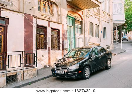 Tbilisi, Georgia - May 20, 2016: The View Of Parked Black Glinting Volkswagen Jetta Car Along The Pavement Of Street With Old Buildings In Summer Day.