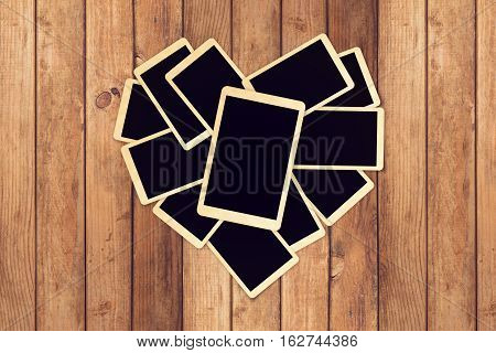 Empty retro instant photos in heart shape on wooden table for photo album design. Valentine's day concept
