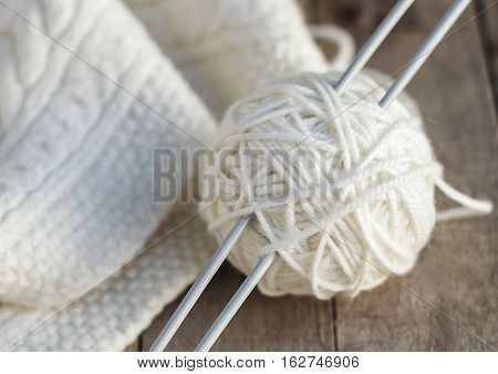 Knitting: ball of soft white wool with needles and knitted scarf. Close up. Selective focus.