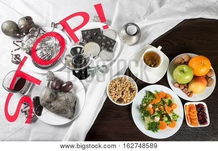 Table with healthy and unhealthy food and alcohol. Sign Stop on the part with harmful dishes and drinks. Dieting after Christmas and New Year celebration.