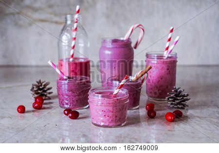 Juicy berry smoothies in glass, jars, bottles on marble background. Christmas cranberry festive theme. Selective focus. Toning.