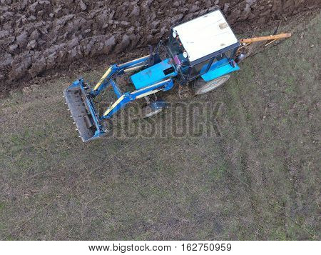 Tractor Plowing The Garden. Plowing The Soil In The Garden