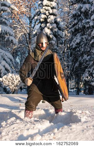 Swordsman in medieval armor the winter forest