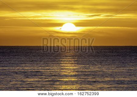 New day at sea. The sun emerges from a bank of low cloud over the horizon at sea.