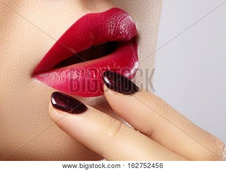 Close-up of woman's lips with fashion red make-up and manicure. Beautiful female full lips with perfect makeup. Classic visage. Part of female face. Macro shot of beautiful make up on full lips