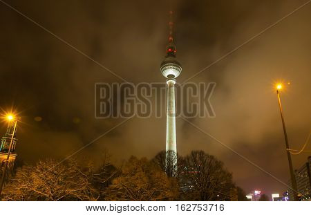 Berlin TV tower (Fernsehturm Berlin) shrouded in clouds at night Germany. Constructed between 1965 and 1969. With its height of 368 metres (including antenna) it is the tallest structure in Germany