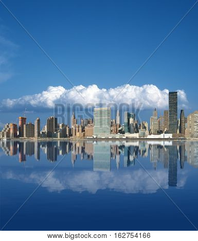 Midtown Manhattan skyline reflected in the waters of the East River. Aspect ratio 6 to 7.