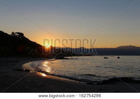 A colorful sunrise at a sandy shore with mountains on background. Summer sunrise. Amazing sunrise.