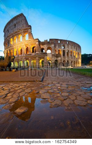 view of Colosseum with puddle illuminated at night in Rome, Italy, toned