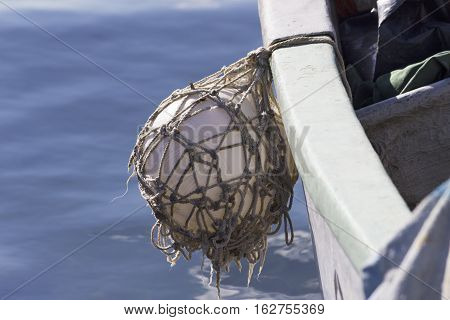fender ball hanging off side of the hull of a fisher boat with blue sea