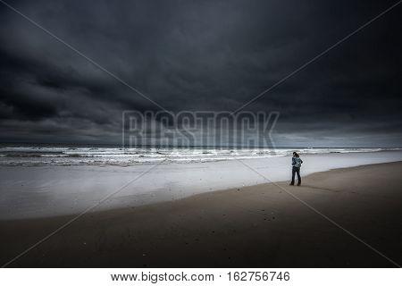 Tourist On South Jetty Beach Oregon Coast Dark Cloudy Day