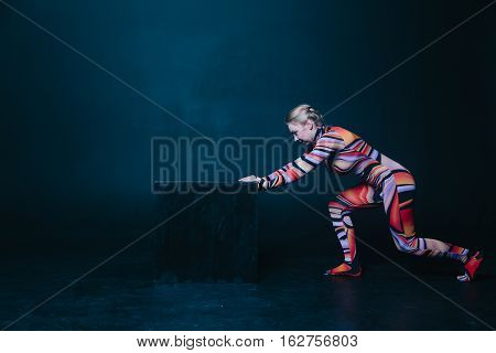 Young flexible blonde circus acrobat posing in studio in costume. Pushing big black cube. Hard work concept. Copy space text.