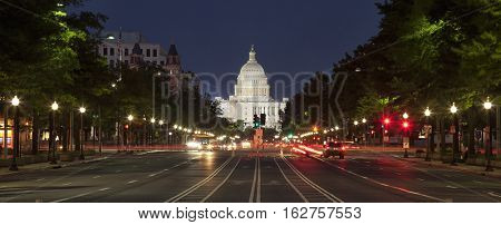 The United States Capitol building and Constitution Avenue in Washington DC at night