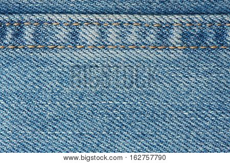 Stitches on light blue jeans background close up