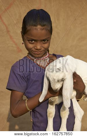MANDU, MADHYA PRADESH, INDIA - NOVEMBER 19, 2008: Young girl holding a small kid goat in the rural hilltop fortress of Mandu in Madhya Pradesh, India
