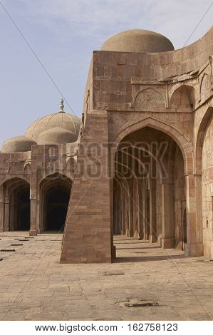 MANDU, MADHYA PRADESH, INDIA - NOVEMBER 18, 2008: Inner courtyard and covered prayer hall of the ancient mosque of Ashrafi Mahal Mosque in the hilltop fortress of Mandu in Madya Pradesh, India. 15th Century AD