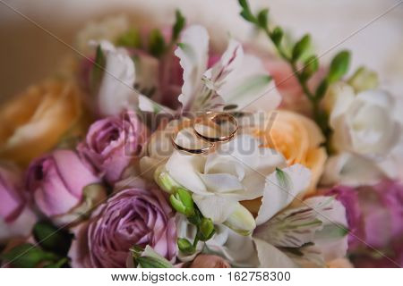infinity sign of the rings wedding rings on a white backgroundwedding bands wedding rings lie on a bouquet of white and pink peach roses a bouquet of roses