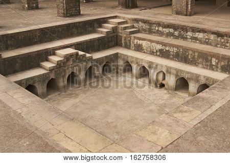 MANDU, MADHYA PRADESH, INDIA - NOVEMBER 18, 2008: Ornate bathing pool at the ancient islamic royal palace of Jahaz Mahal. Mandu, Madhya Pradesh, India. 16th Century AD