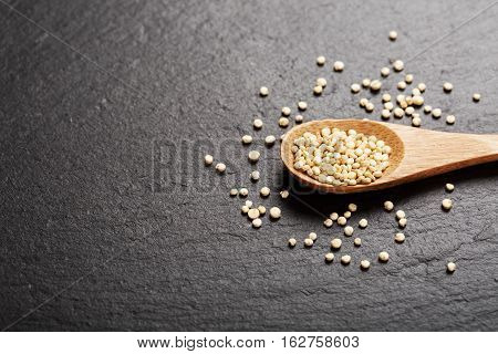 Raw white quinoa seeds in wooden spoon on black stone background. Concept of healthy and gluten free food.