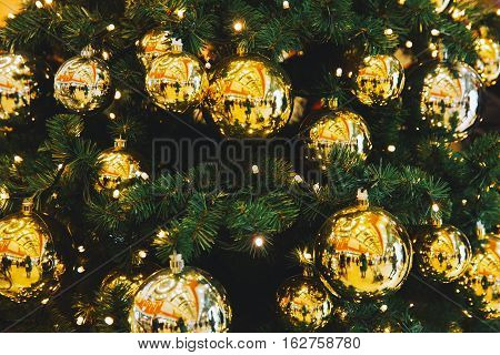 Christmas yellow balls hanging on a Christmas tree. Christmas tree background. Christmas in Europe. Christmas New Year decorations in shopping center