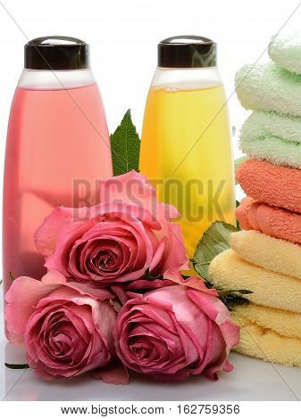 Multicolored items for baths, saunas, spa: shampoo, towels, flowers roses on a white background