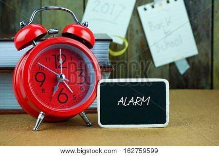Alarm inscription written on chalkboard, red alarm clock, book on desk. Notes and old wooden background. Time concept.