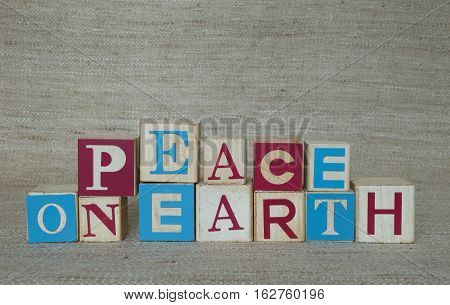 Red, medium blue and off white wooden blocks that spell Peace on Earth. Blocks vary in sizes and lettering. Photographed against a tan woven fabric at eye level.