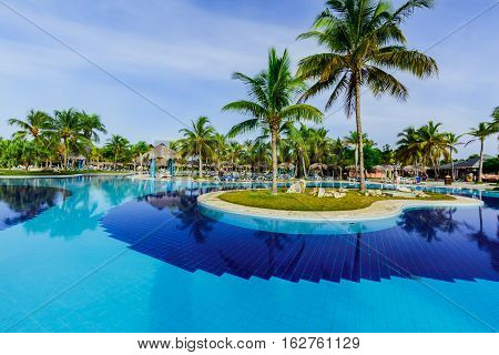 Holguing Province, Playa Pesquero Hotel, Cuba, Aug. 31, 2016, amazing gorgeous inviting view of luxury swimming pool and hotel grounds in tropical garden in early morning time
