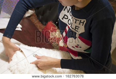 Young Woman Christmas wrapping or Boxing Day returning gifts in ugly Christmas Sweater