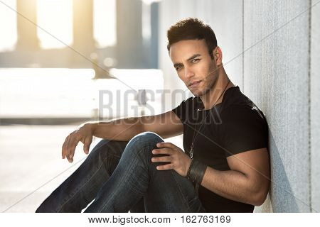 Young handsom man sitting leaning on the wall and sitting wearing casual street style outfit. Male fashion model man in black t-shirt dark blue jeans and leather braclet posing outdoors.