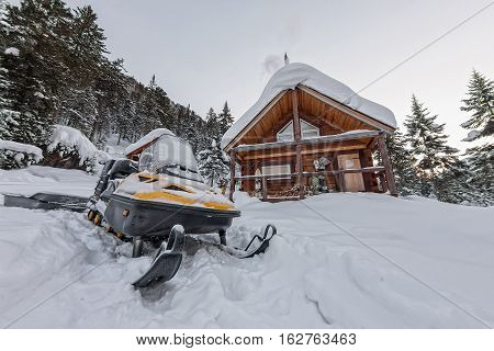 Snowmobile From House Chalets In Winter Forest With Snow In Mountains