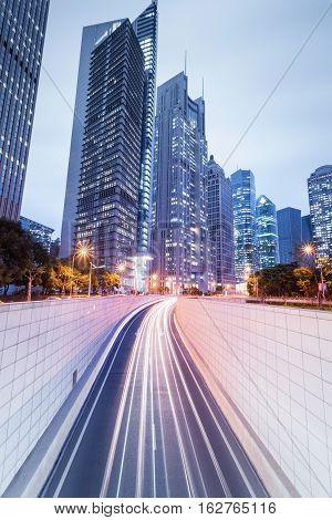 city tunnel road in nightfall with modern financial buildings at shanghai