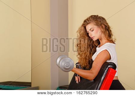 Sweetheart girl doing exercise for biceps with hand weights. Working with free weight. Healthy lifestyle concept. Fitness.