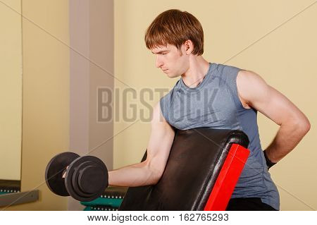 Man doing exercise for biceps with dumbbell. Working with free weight. Healthy lifestyle concept. Fitness.