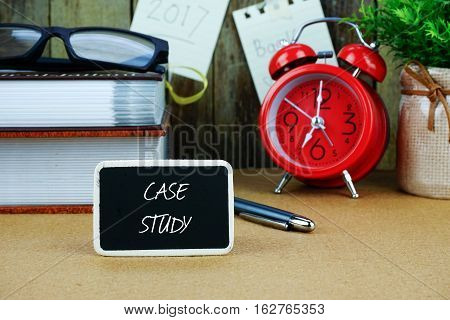 Case study inscription written on chalkboard. Red alarm clock, book, spectacle, notes at background.