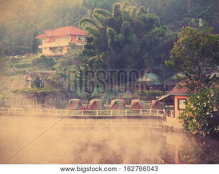 Village and lake landscape view in the morning with mist at Rak Thai Village Mae Hong Son Province Thailand vintage filter effect.