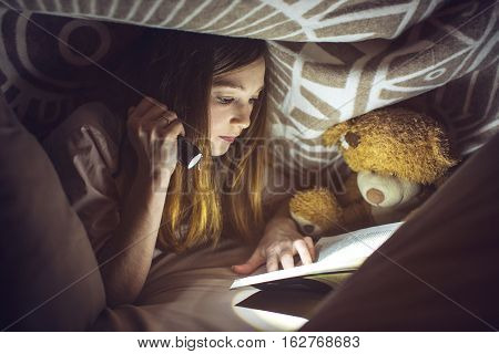 Young Girl Reading A Magic Book In The Dark