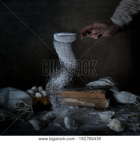 female hand sifts the flour on a wooden table. dark background