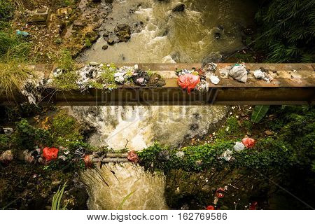 A dirty river flow with plastic waste photo taken in Bogor Indonesia java