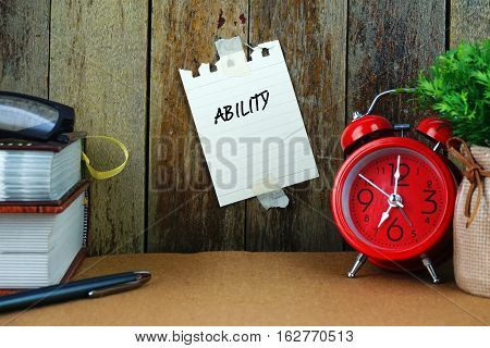 Ability text written on sticky note. Book, pen, spectacle and red clock on brown desk. Education and business concept.