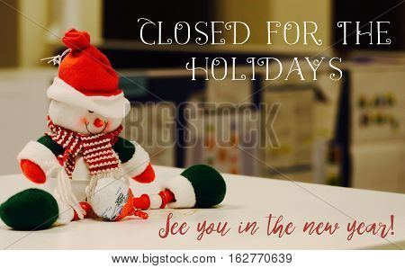 Closed for the Holidays background New Year and Christmas holidays office hours with copy space festive image with cute snowman and office cubicles in customer service center