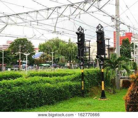 traffic lamp light for train commuter line with tree and green bush and electric cable in bogor indonesia photo