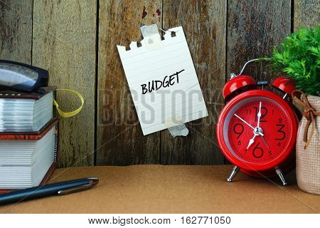Budget text written on sticky note. Book, pen, spectacle and red clock on brown desk. Education and business concept.