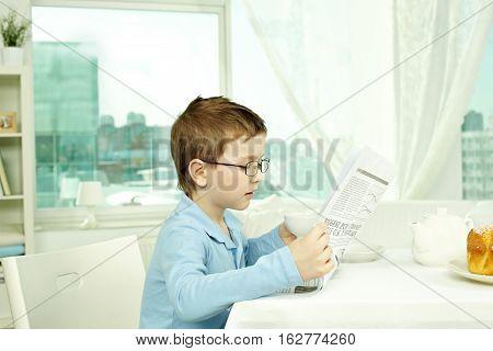 Little boy inn glasses reading paper at home