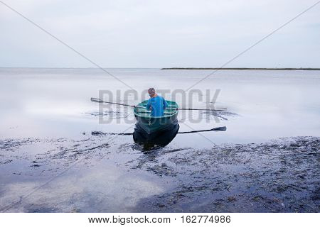 Man Sailing On A Small Rowing Boat Along The Sea Coast