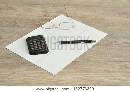 A calculator pen reading glasses and a piece of paper displayed on a wooden background