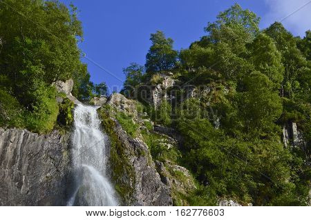 The edge of a tropical waterfall with blue sky and foliage surrounding, Aber falls abergwyngregyn wales