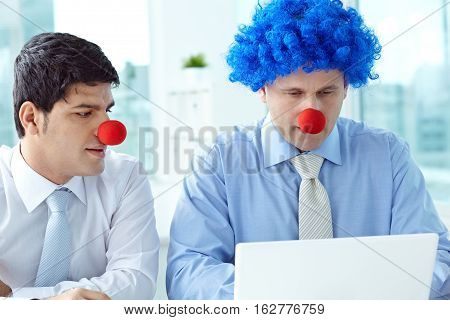 Two businessmen in clown wig and noses working in office