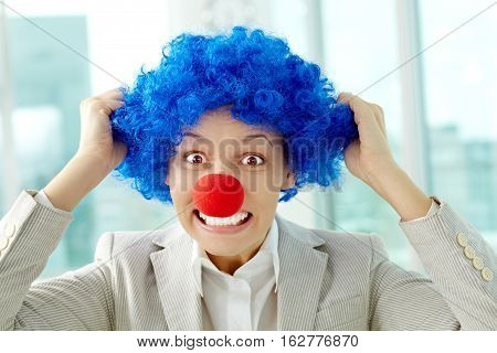 Portrait of female manager in clown wig and nose tearing hair out