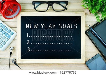 Top view of earphone, calculator, alarm clock, spectacle, notebook, pen, smartphone and chalkboard written with NEW YEAR GOALS.